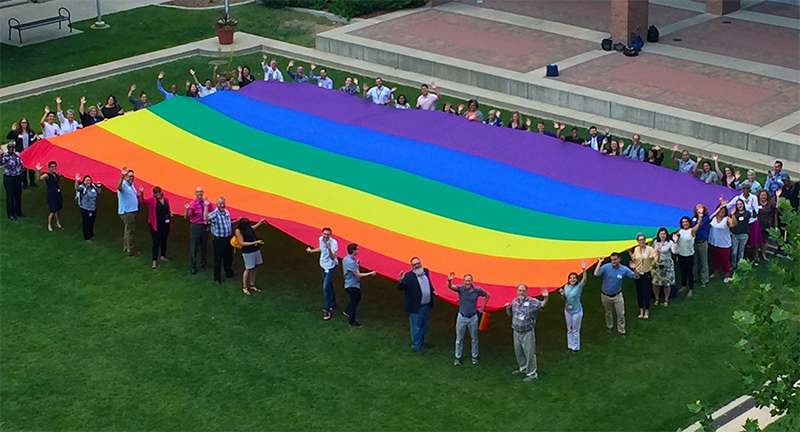 Attendees pose with a 30-by-50-foot rainbow flag at Something Queer 2018.