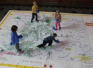 Elementary students explore a walkable map of Colorado.