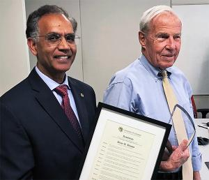 Former Council Chair Ravinder Singh presents President Bruce Benson with the Leadership in Public Higher Education Award.