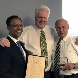 David Thompson receives his award from Faculty Council Chair Ravinder Singh and CU President Bruce Benson.