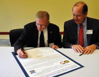 Theodore Drier (left), senior director, intelligence programs and national security solutions, Dyncorp International, and Martin Wood, senior vice chancellor, University Advancement, sign a statement of support with the Army Reserve Feb. 10.