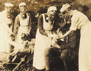 German nurses taking care of wounded soldiers, all (including the nurses) wearing gas masks.