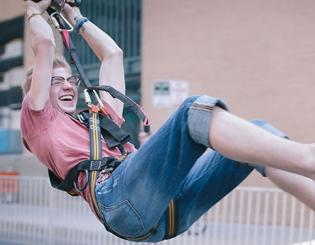 Kelper Maurer-alcala rides the zip line down Lawrence Street at the CU Denver Block Party.