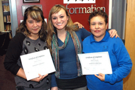"Tutor Ashley Haines stands with graduates of ""Computer Basics"" Angelica Reaves, left, and Blanca Gastulo, right."
