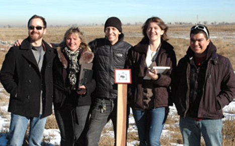 Digital Design students, from left, Shawn Jenkins, Seth Chaps, Sarah Torp and David Bonilla stand with Professor Michelle Carpenter, second from left, at the Rocky Mountain Arsenal as they demonstrate their augmented reality project for U.S. Fish & Wildlife Service officials.)